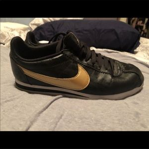 Women's rose gold and black Nike Cortez